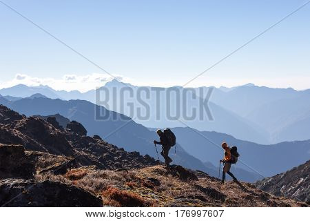 Two Men walking on rocky slope carrying Backpacks using trekking Sticks dressed in alpine Jackets and hiking Pants. Layered Mountains View beside Silhouetted of People