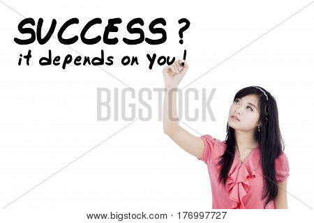 Beautiful Asian woman writes a motivation words on a transparent screen isolated on white background