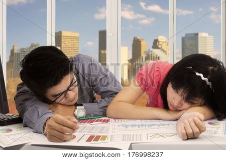 Picture of business people feels sleepy while working with a computer and paperwork on the desk