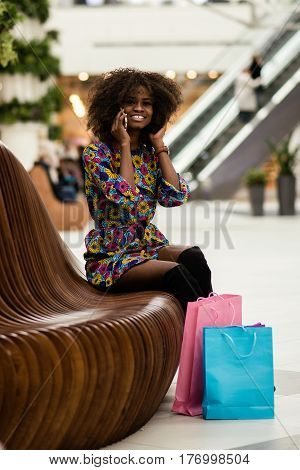 Afro-american girl talking on the phone in a shopping mall. Happy girl with curly hair.