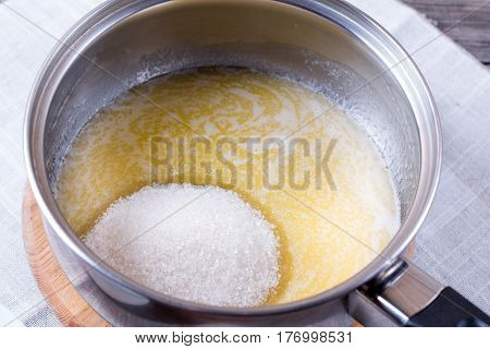 Sugar and butter in a skillet on a wooden background