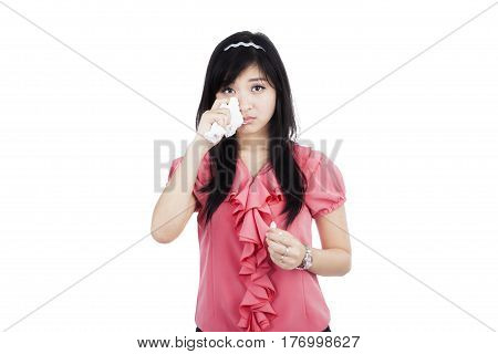 Close up of a young businesswoman crying in the studio and wiping her tears with a tissue
