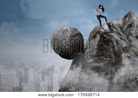 Young businesswoman is pulling big rock with a chain on top of a cliff