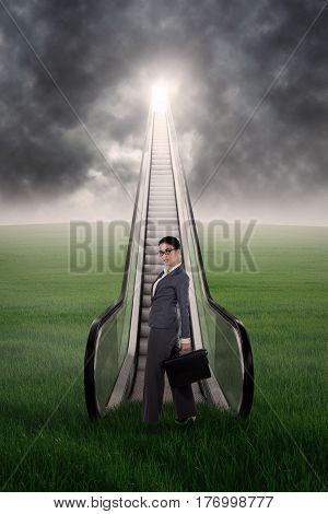 Businesswoman standing on the meadow with escalator under cloudy sky