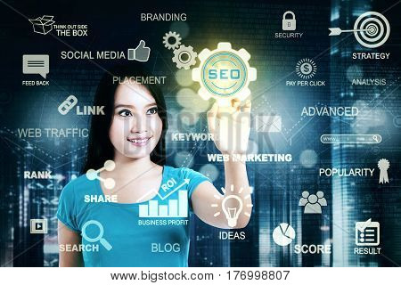 Picture of a young casual woman pressing a virtual SEO icon on the futuristic screen. SEO concept