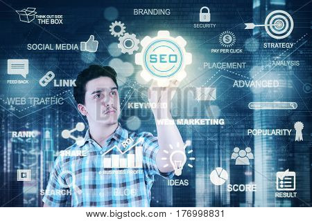 Photo of a caucasian man pressing a virtual SEO button on the futuristic screen. SEO concept