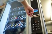 sell, technology and consumption concept - hand pushing button on vending machine operation panel poster