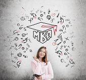 Portrait of a young girl with a notebook standing near a concrete wall with a black and red MBA sketch on it. poster