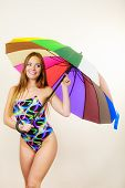 Fashion great outfits for summer concept. Happy woman with long brown hair posing in swimsuit and colorful umbrella poster