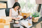 Young Asian small business owner working at home office using mobile phone and taking note on purchase orders. Online marketing packaging delivery startup SME entrepreneur or freelance woman concept poster
