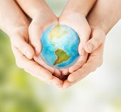 earth day, nature, conservation, environment and ecology concept - close up of woman and man hands holding planet over green natural background poster