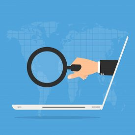 businessman hand with magnifying glass from laptop computer on world map background. Online Scam business concept.