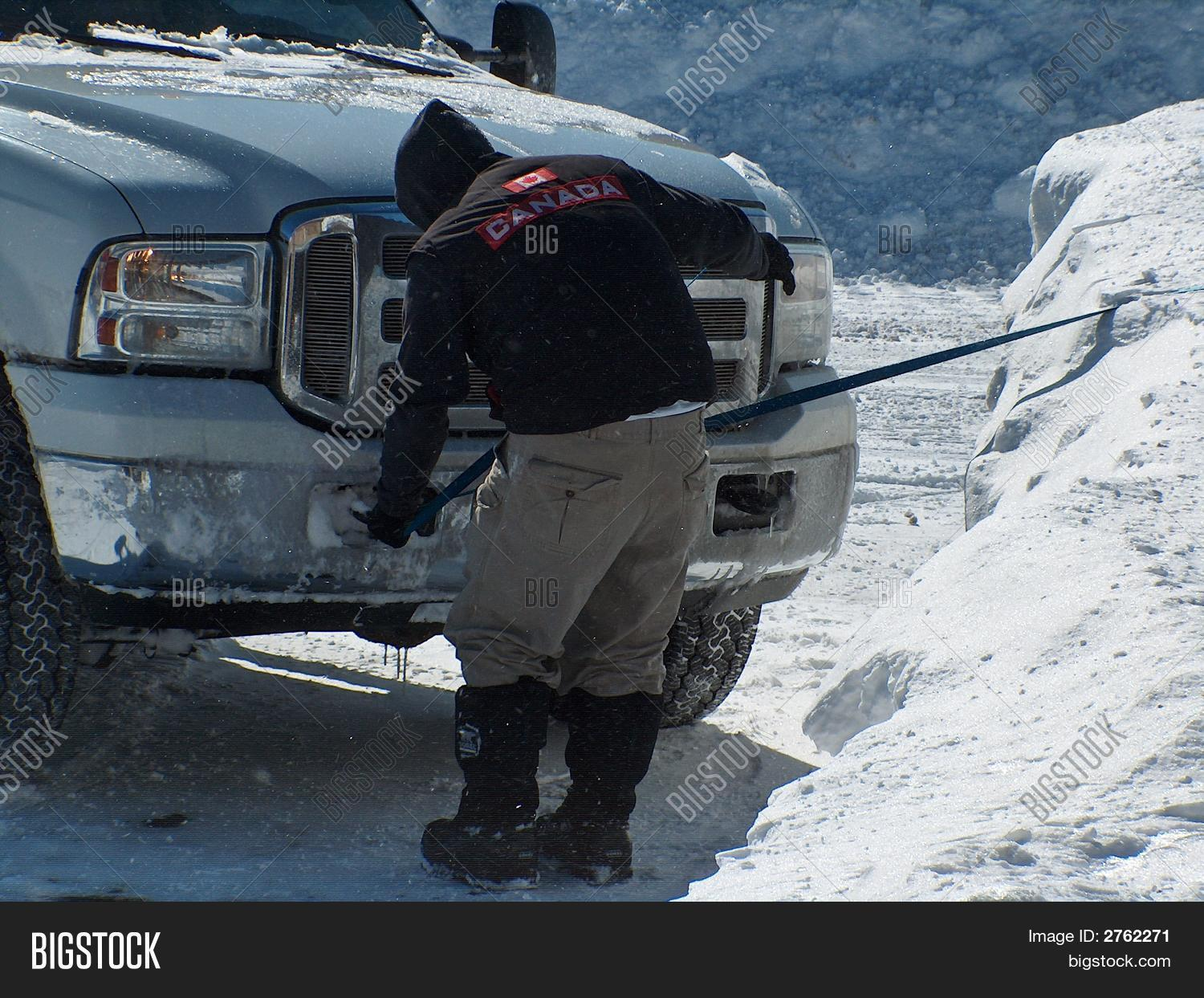 A man hooks up a line to front of a truck to pull something out of the snow