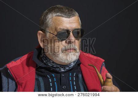 Nice Low Key Portrait Of Senior Man In Black Eyeglasses Holding Tobacco-pipe