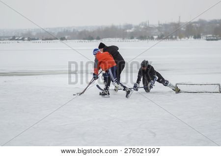 Dnipro, Ukraine - January 28, 2018: Three Ordinary People Playing Hokey On A Frozen River Dnipro In