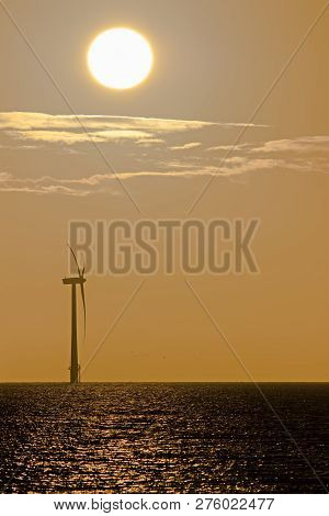 Global Warming And Climate Change. Wind And Solar Power. Solitary Offshore Wind Turbine At Sunrise O