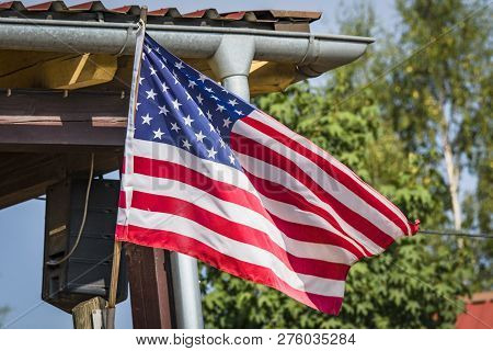 American Flag On A Porch Outside A Small Cabin In The Wild West In The Summer