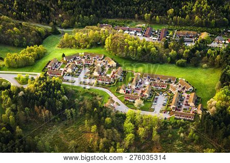 Small Village Seen From Above Surrounded By Forest On A Sunny Day