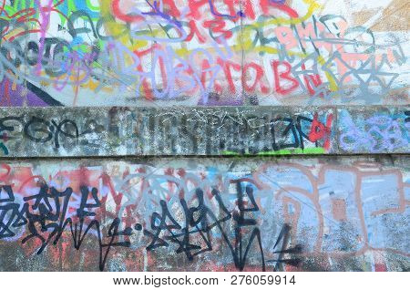 Fragment Of Graffiti Tags. The Old Wall Is Spoiled With Paint Stains In The Style Of Street Art Cult