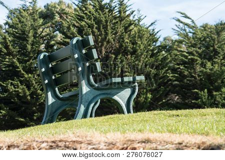 A Green Park Bench Sits On Top Of A Grassy Hill, Unoccupied, On A Sunny Day