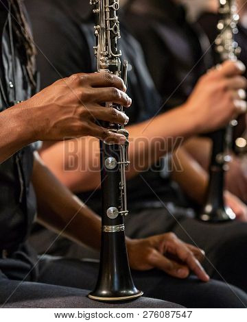 An African American Man Holds His Clarinet At Rest During Musical Symphonic Performance. Woodwind Se