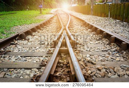 train tracks on gravel, two of railways tracks merge  with sunset background, concept of success poster
