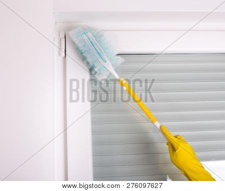 Woman With Protective Gloves Dusting Corners And Walls In Room