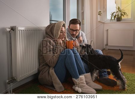 Young Couple In Jacket And Covered With Blanket Sitting On Floor Beside Radiator With Dog And Trying