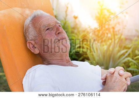 Old Man Resting On Sunbed In Garden. Depression In Senior Age