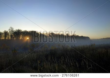 Beautiful Thick Fog Sunrise Autumn Fall Landscape Over Fields With Treetops Visible Through Fog