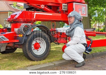 Insect Killer In Protective Working Clothes Operates Aerial Platform