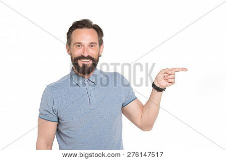 Portrait Of Optimistic Bearded Man In Casual Clothes Pointing Sideways While Looking At You With Bro