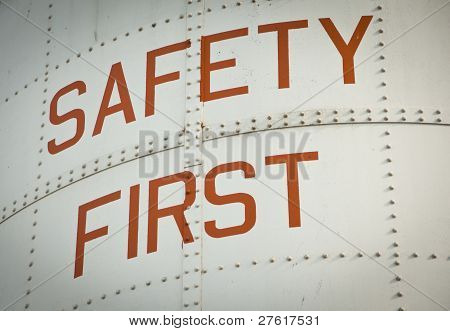 A Metal work sign painted with the words SAFETY FIRST. poster