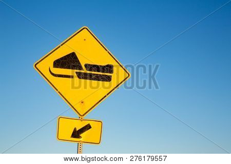 Yellow road sign for Snowmobile trail, with blue sky background and space for text. Quebec Province, Canada.