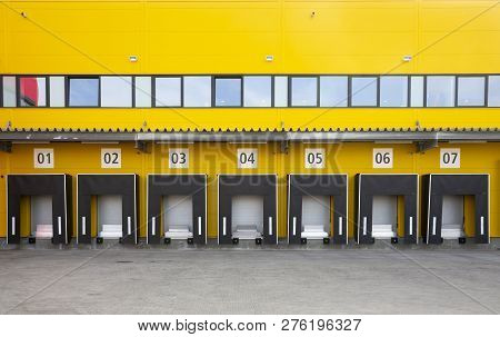 Seven Truck Loading Docks At A Distribution Warehouse. Distribution Hub For Sorting Packages And Par