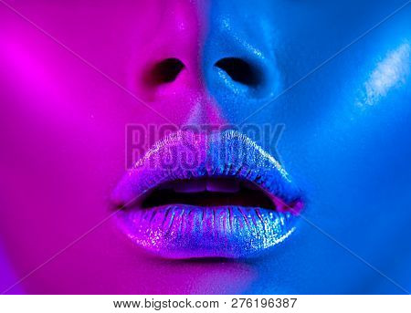 High Fashion model metallic silver lips woman in colorful bright neon blue and purple lights, beautiful girl face closeup, trendy glowing make-up, colorful make up. Glitter Vivid neon makeup. Art