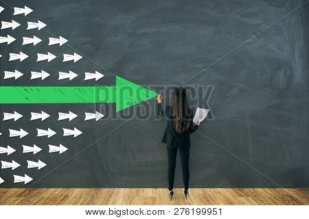 Back View Of Businesswoman Drawing Arrows On Wall. Leadership And Success Concept
