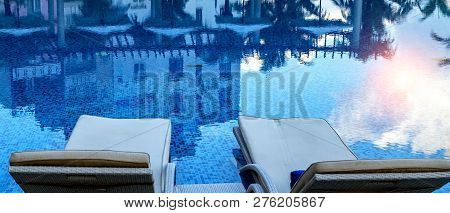 Sun Blue Sky And Green Palm Trees Reflections In Hotel  Swimming Pool With Sunlight Clear Blue Water