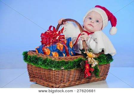 Baby Santa. Cute little girl dressed as Santa Claus sitting in a wicker basket with a gift. Basket d