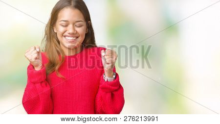 Young beautiful brunette woman wearing red winter sweater over isolated background excited for success with arms raised celebrating victory smiling. Winner concept.