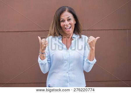 Beautiful middle age hispanic woman at over brick wall on a sunny day screaming proud and celebrating victory and success very excited, cheering emotion