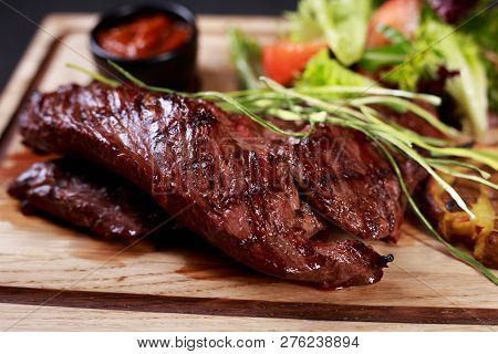 Juicy Medium Rare Skirt Steak, Hanging Tender Steak Served With Vegetable Salad And Potatoes On Boar