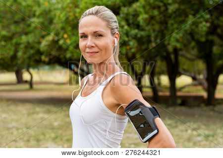 Portrait of athletic mature woman resting after jogging. Beautiful mid blonde woman running at park on a sunny day. Female runner listening to music while jogging and looking at camera.