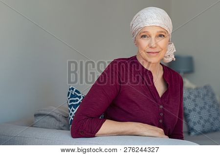 Mature woman with cancer in pink headscarf smiling sitting on couch at home. woman suffering from cancer sitting after chemotherapy sessions. Portrait of mature lady facing side-effects of hair loss.