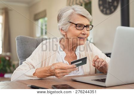 Happy senior woman making online payments using laptop. Smiling old grandmother doing shopping on ecommerce with credit card. Pensioner holding debit card for internet banking.