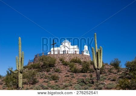 Monastery Chapel And Cross On Hilltop With Cactus In Desert