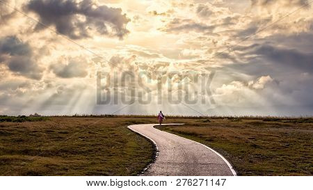A Person Walking Alone Along S-shape Path. The Sun Produces Amazing Light Rays Across The Sky. The I