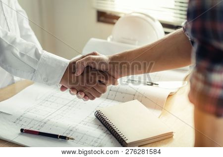 Construction Worker Shaking Hands With Customer After Finishing Up Business Meeting To Greeting Star