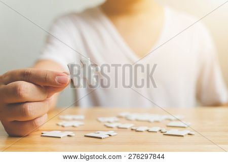 Hand Of Male Trying To Connect Pieces Of White Jigsaw Puzzle On Wooden Table. Healthcare For Alzheim