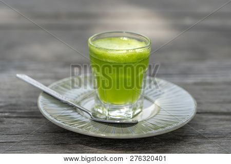 Wheat Grass Juice Natural Drink With Fresh Wheatgrass In Glass On Old Wooden Table Background. Organ